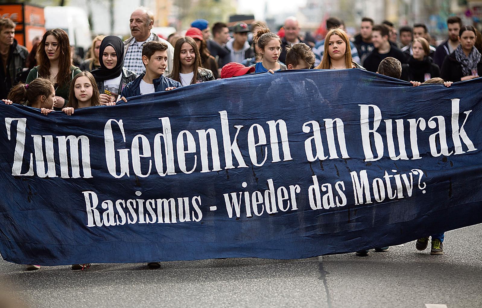 """""""Zum Gedenken an Burak - Rassismus - wieder das Motiv?"""" steht am 05.04.2014 in Berlin bei einer Demonstration zum Gedenken an den 22-jährigen Burak Bektas auf einem Transparent. Bektas wurde in der Nacht zum 5. April 2012 in Berlin-Neukölln erschossen. Am Jahrestag seines Todes wollen Freunde und Eltern daran erinnern, dass bis heute vom Täter jede Spur fehlt. Foto: Florian Schuh/dpa +++(c) dpa - Bildfunk+++"""